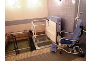 リハビリホームまどか川口本町 車椅子に座ったまま湯船に浸かれるリフト付浴室です。安全にご入浴いただくため、手すりやシャワーチェアも設置しております。